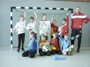 Auf dem Bild präsentieren unsere Fußballer zusammen mit ihrem Trainer, Helmut Hermsen, die Kooperationspräsente des DFB.